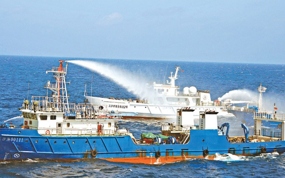 """China's maritime militia fishing vessels """"Qiongsanshayu 00111"""" and """"Qiongsanshayu 00310"""" participates in a firefighting and rescue exercise in waters off the Phu Lam (Woody) Island in Vietnam's Hoang Sa (Paracel) archipelago on July 14, 2016 in this photo by a Chinese maritime safety administration."""
