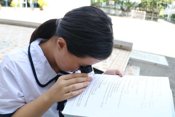 Van Nhu uses magnifying lens to read. Photo: Trong Nhan / Tuoi Tre