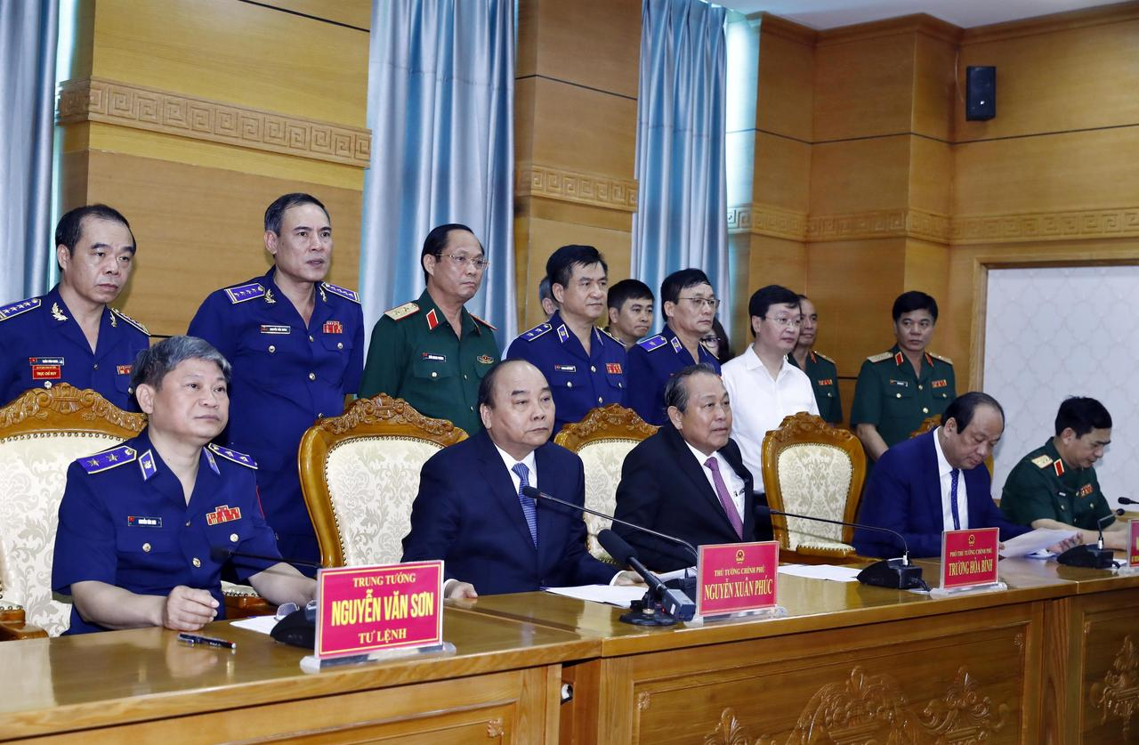 Vietnam's Prime Minister Nguyen Xuan Phuc (2nd L, front) and Deputy Prime Minister Truong Hoa Binh (2nd R, front) speak with sailors of Coast Guard Force on field via video call during their visit to Coast Guard Command in Hanoi, Vietnam July 11, 2019. Photo: Vietnam News Agency