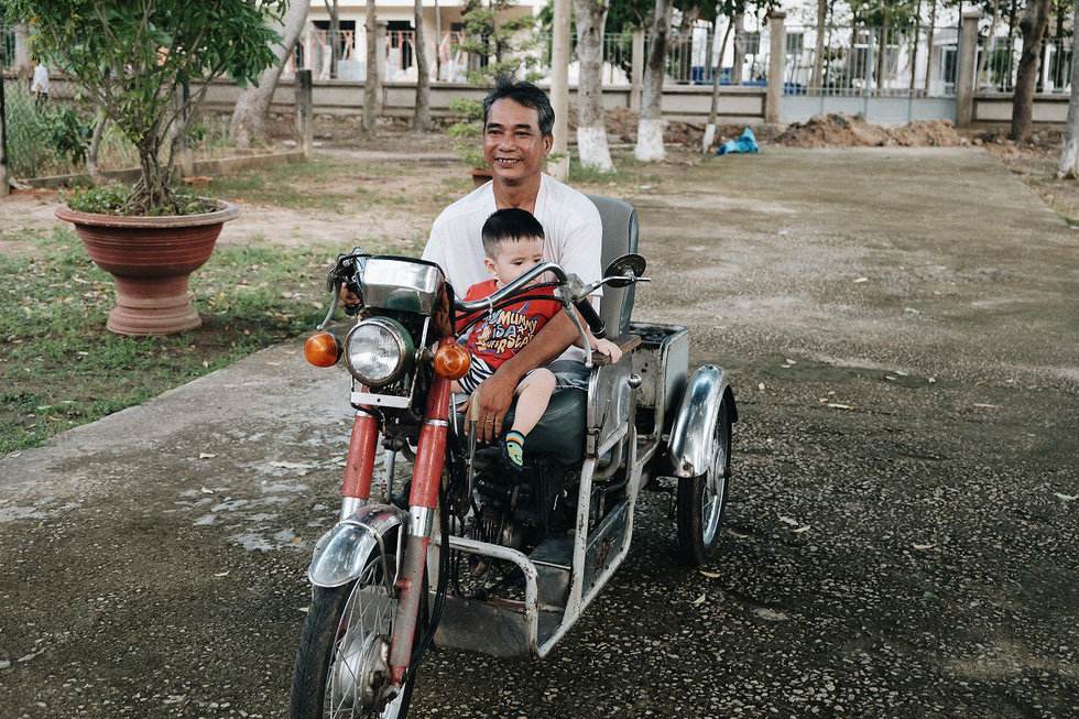 Post-war invalid Nguyen Duy Minh is seen with his grandchild at the Long Dat Wounded Soldiers' Nursing Center located in Ba Ria – Vung Tau Province, southern Vietnam. Photo: Mai Thuong / Tuoi Tre