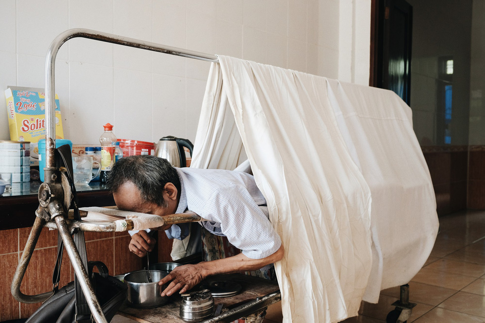 Tran Toan, a post-war invalid from the 1979 southwest border defense war with the lower half of his body atrophied and losing of feelings, has a meal on a special bed made to serve his daily personal activities. Photo: Mai Thuong / Tuoi Tre
