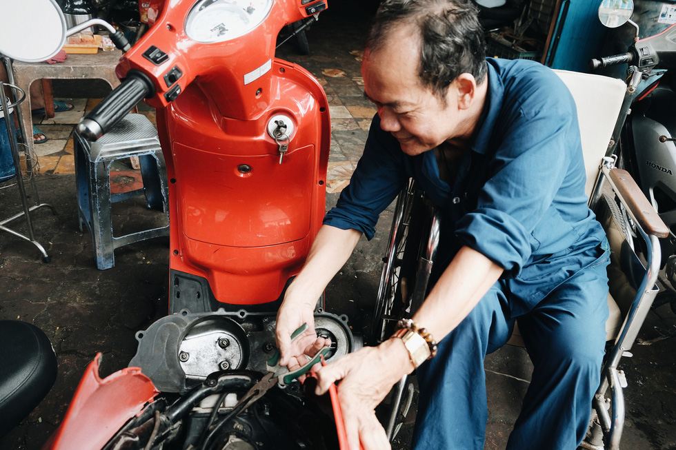 Phan Van Tinh, a post-war invalid from the 1979 southwest border defense war with the lower half of his body atrophied and losing of feelings, works as a motorbike mechanic. Tinh has done charity works for nearly 20 years, giving vocational training to undisciplined young people, giving free food to the poor twice a month, giving books to disadvantaged students. Photo: Mai Thuong / Tuoi Tre