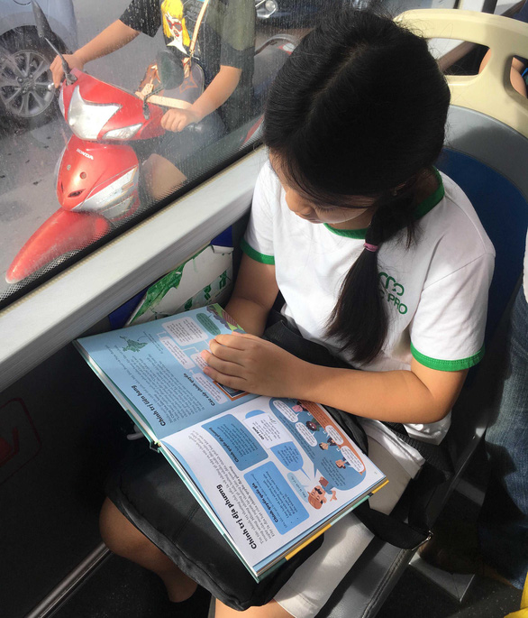 Nguyen Nguyet Linh reads a book on a bus. Photo: supplied