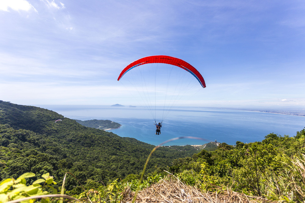 An athlete paraglides from the top of Son Tra Mountain, Da Nang Province at Da Nang Open Paragliding Championship 2019 on July 27, 2019. Photo: Pham Hung / Tuoi Tre