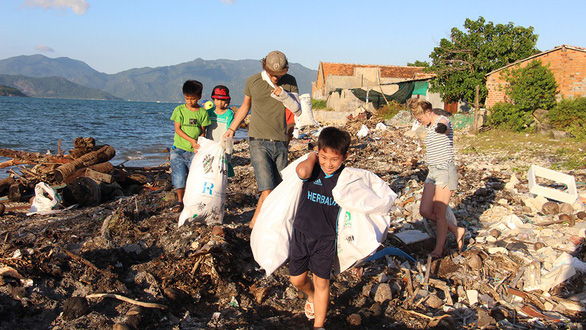 Local children join hands with Trashpackers members to clean up the beach. Photo: Tuoi Tre