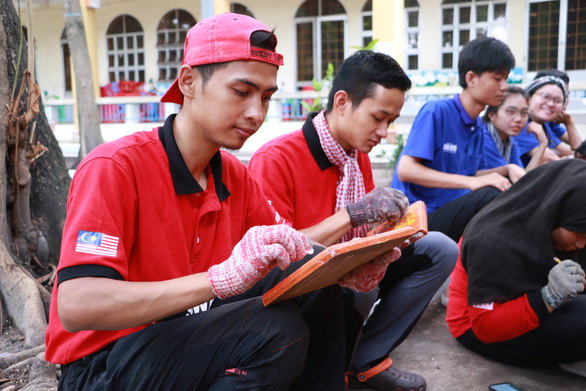 Malaysian volunteers prepare name tags for their homemade tree pots. Photo: Binh Minh / Tuoi Tre
