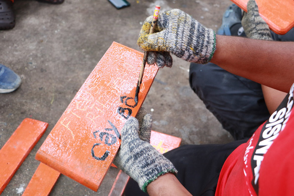 A Malaysian volunteer paints the name of a tree on a homemade sign. Photo: Binh Minh / Tuoi Tre