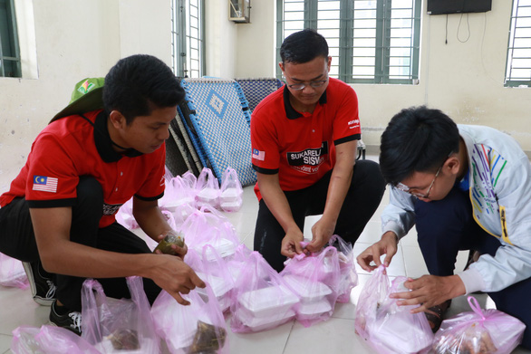 Malaysian and Vietnamese volunteers prepare meals for people in need. Photo: Binh Minh / Tuoi Tre