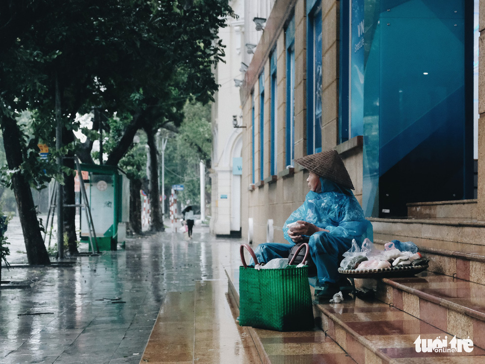 A street food vendor sits in front of a building as she hopefully waits for a customer. Photo: Mai Thuong / Tuoi Tre
