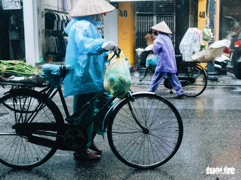 Hawkers sell their products on the rainy morning. Photo: Mai Thuong / Tuoi Tre