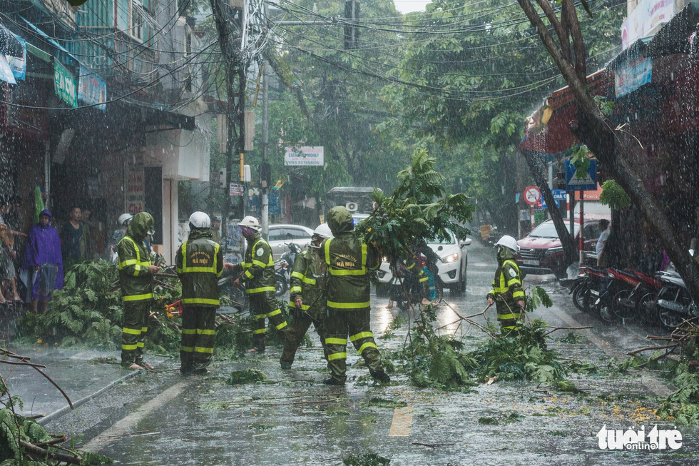 Employees of the Hanoi Greenery Park Company remove broke tree branches from the roadway. Photo: Dinh Minh / Tuoi Tre