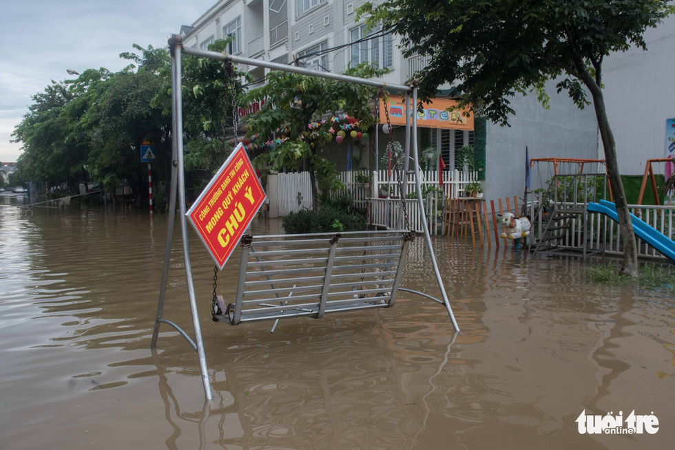 A heavily flooded location is marked by a warning sign.