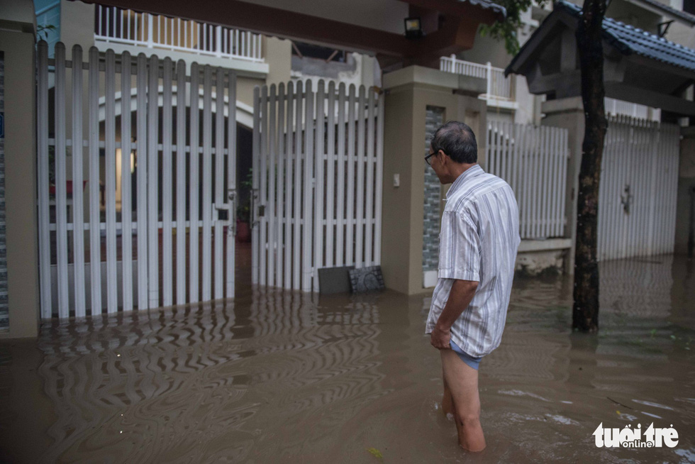 A local resident walks on a flooded street in front of his house.