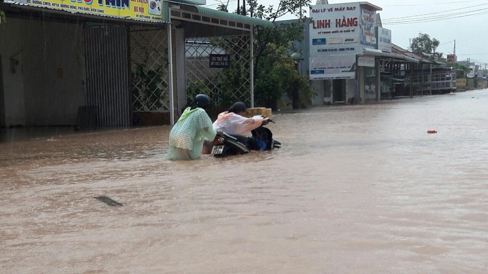 Two women push a motorbike on a heavily flooded street.