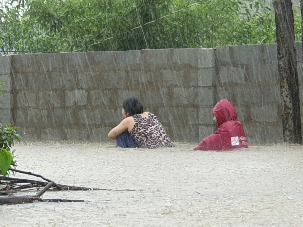 Residents struggle to travel on a submerged neighborhood.