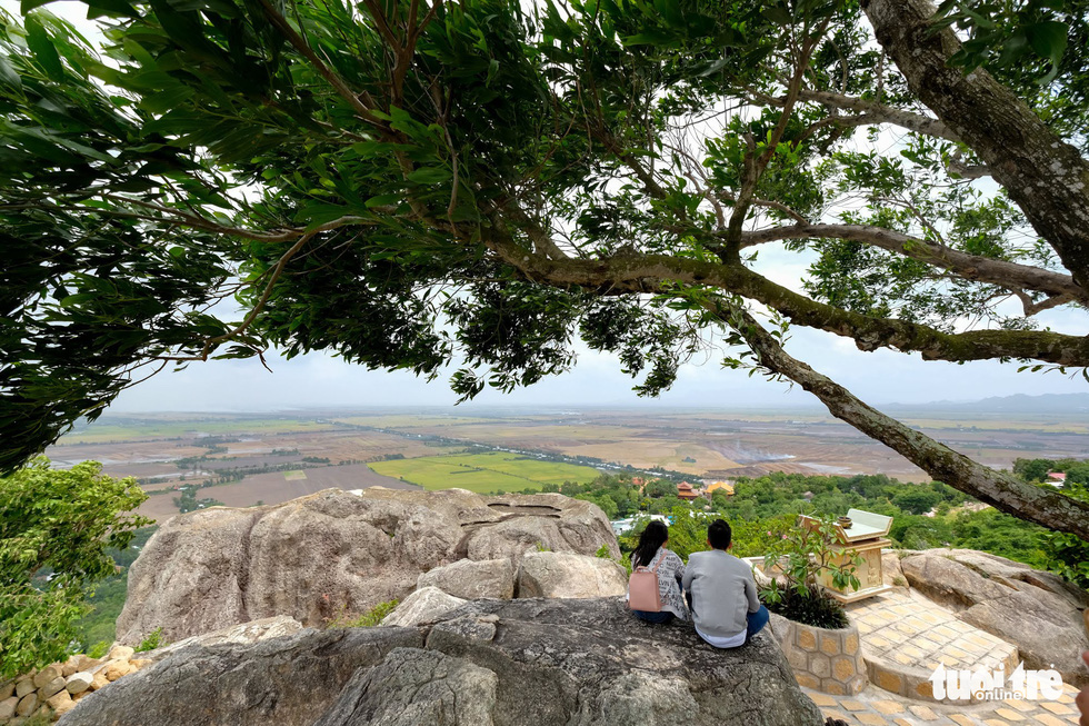 Two visitors look down to admire the landscape surrounding Sam Mountain. Photo: Tuoi Tre