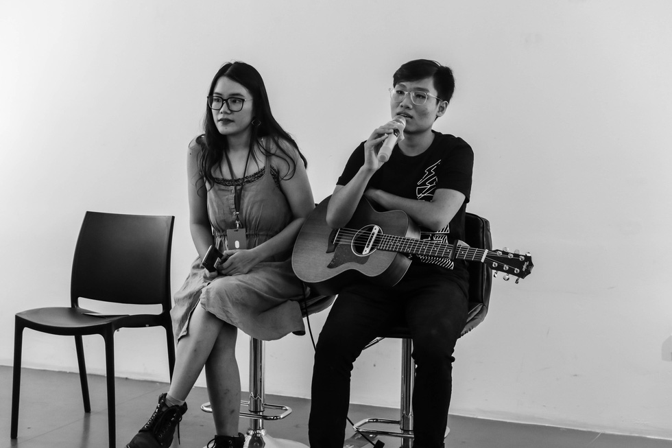 Tram Anh (left) sits on the stage during a musical performance. Photo: supplied