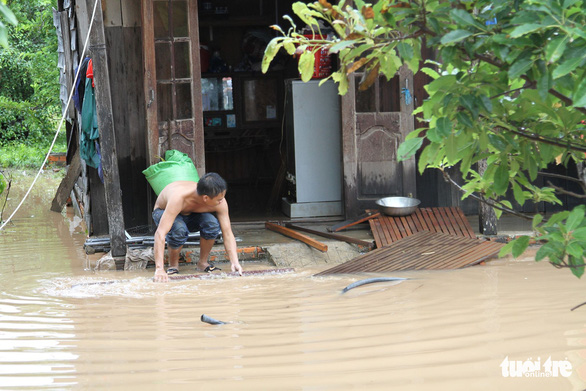 A man tries to protect his home from the flooding. Photo: Tr.Tan / Tuoi Tre