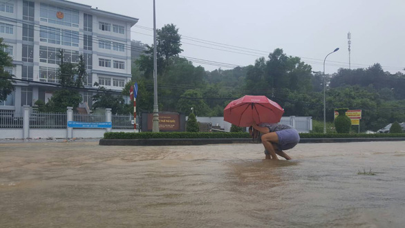 A resident struggles to walk on a flooded street. Photo: Van Tien / Tuoi Tre
