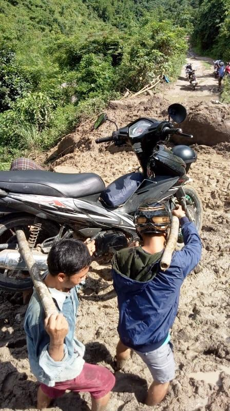 Teachers carry a motorbike across a muddy path to school in Muong Lat District in Thanh Hoa Province, Vietnam. Photo: Lang Van Long