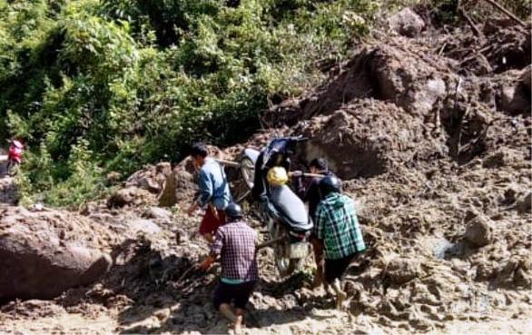 Vietnam teachers carry motorbikes across muddy paths after storm cut off access to school
