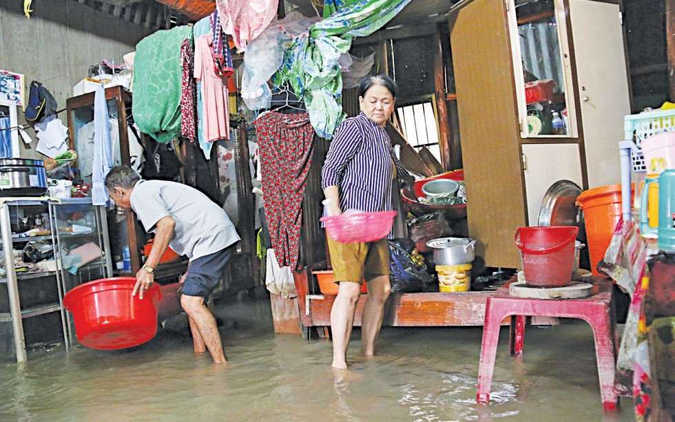 Residents struggle to walk in their flooded house.