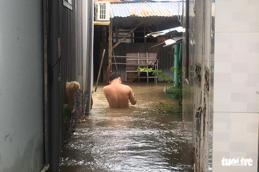A man walks among waist-deep water.