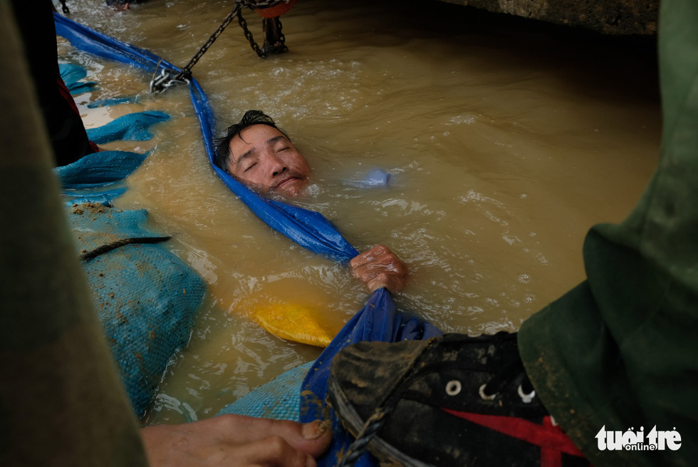 A man dives into the floodwater to fix the dam.