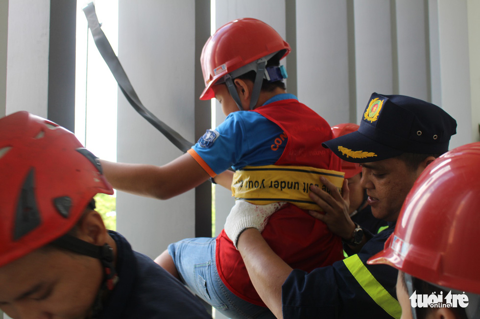 A child practices exit from a building by using rescue rope during a firefighting training. Photo: Le Van Quang / Tuoi Tre