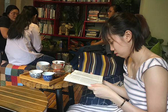 A young woman reads a book at a tea house in Ho Chi Minh City. Photo: Minh Phuong / Tuoi Tre