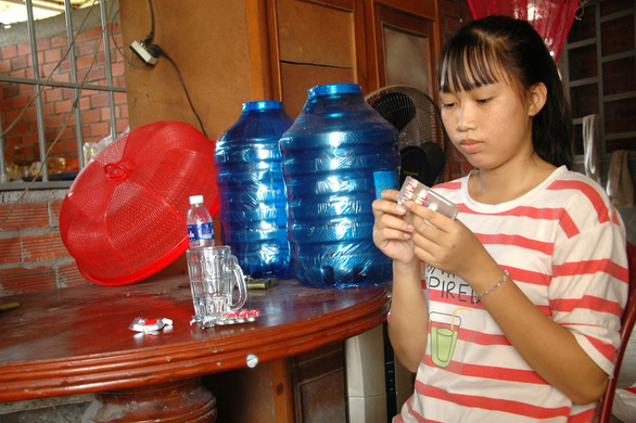 Lam Thi Tuyet Nghi prepares to take medicines for her blood disorder at her house in Ben Tre, southern Vietnam. Photo: Lu The Nha