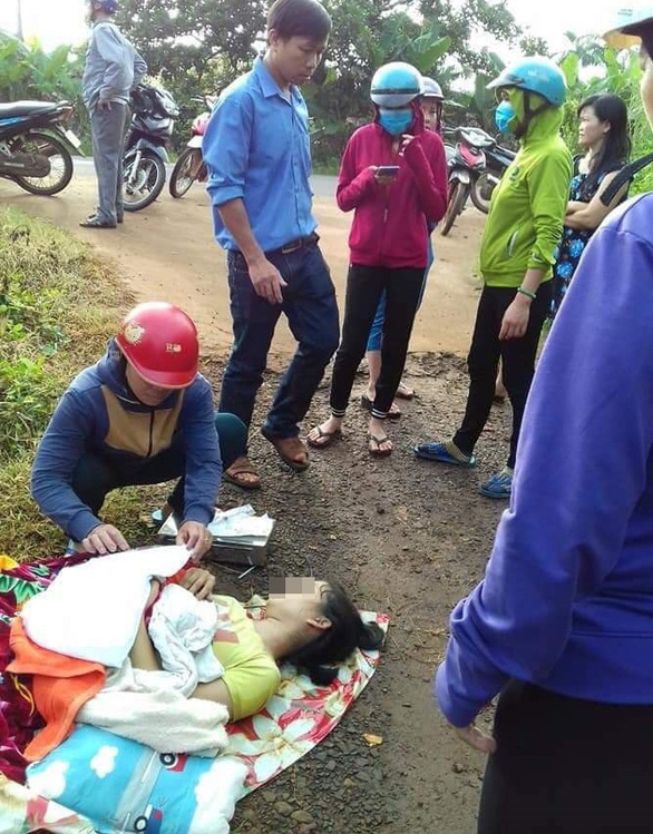A woman clings to her dead newborn son as she lies on the side of a road in Binh Phuoc Province, Vietnam after being forced off a rental car on August 17, 2019. Photo: Tuoi Tre