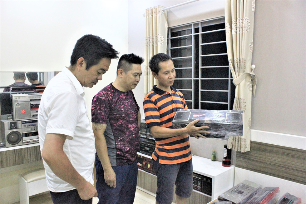 Nguyen Xuan Thuy (right) introduces his collection to Nguyen Manh Ha (left) and Dang Dai Hung, other members in radio lovers club in Hanoi. Photo: Thien Dieu / Tuoi Tre