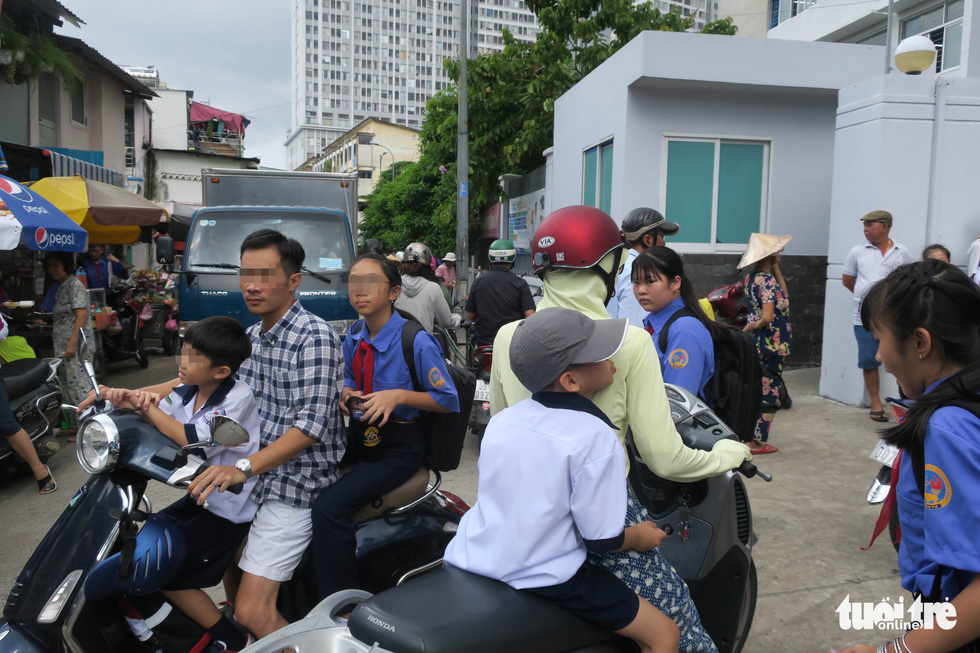 Parents pick up children from a school in District 4, Ho Chi Minh City, wearing no helmet, on August 22, 2019. Photo: Quang Dinh / Tuoi Tre