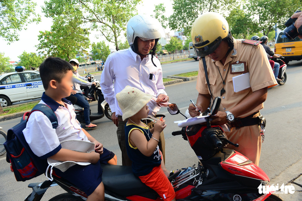 Police stop a man for carrying two children without them wearing helmets on Vo Van Kiet Street in District 5, Ho Chi Minh City.