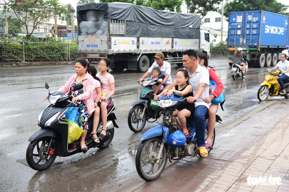 Parents and children wearing no helmet travel wrong way on a section of National Highway 1 passing through District 12, Ho Chi Minh City. Photo: Quang Dinh / Tuoi Tre