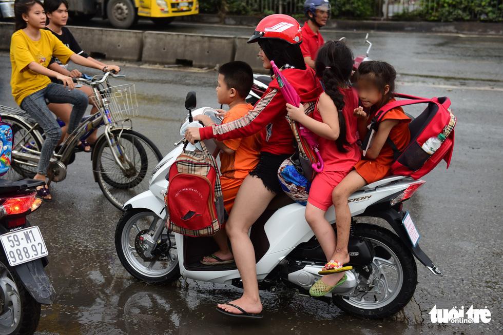 In Vietnam, parents take children to school defying compulsory helmet rule