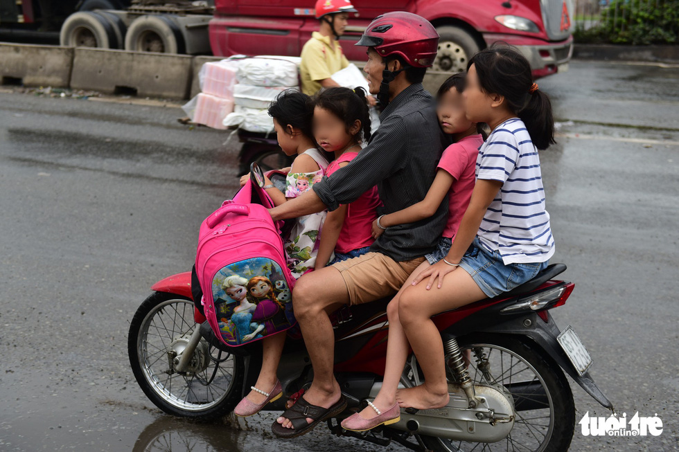A man carries four children, who wear no helmet, on one vehicle in Ho Chi Minh City. Photo: Quang Dinh / Tuoi Tre