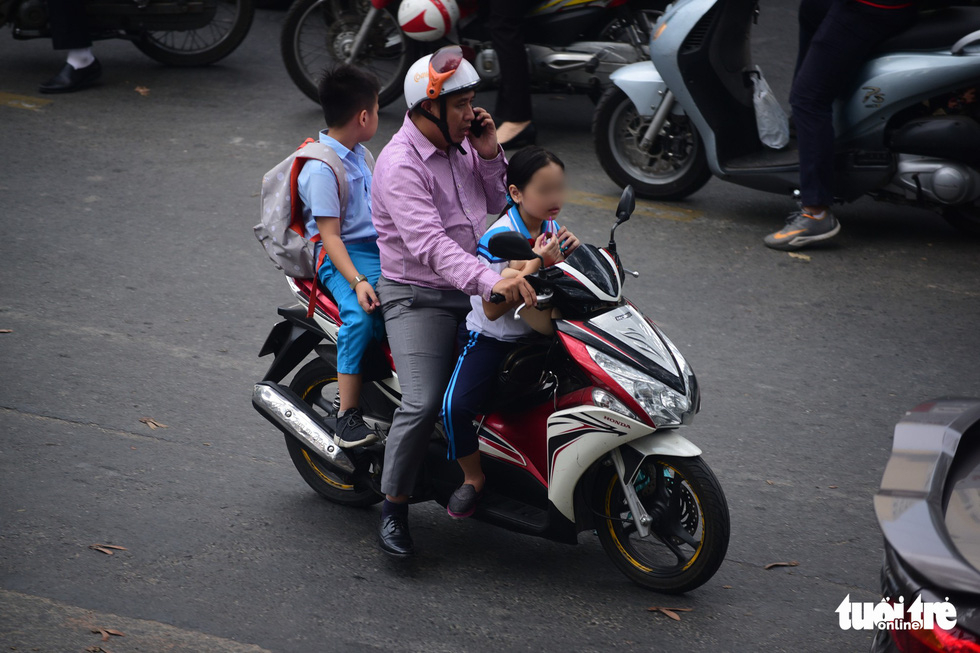 A man carries two children, who wear no helmet, on Nguyen Thi Minh Khai Street in District 3, in Ho Chi Minh City. Photo: Quang Dinh / Tuoi Tre