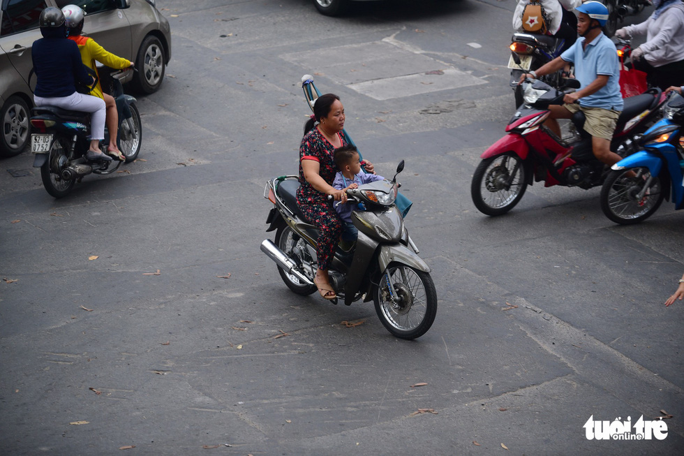 A woman carries her child on a street in Ho Chi Minh City, wearing no helmet. Photo: Quang Dinh / Tuoi Tre