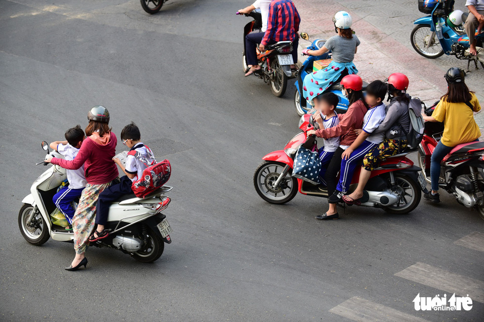 Parents wear helmets, while their children don't on Nguyen Binh Khiem Street in Ho Chi Minh City. Photo: Quang Dinh / Tuoi Tre