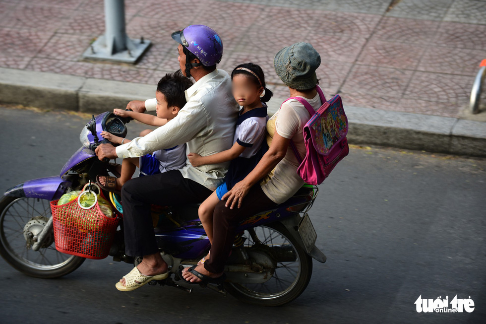 Parents wear helmets, while their children don't on a street in Ho Chi Minh City. Photo: Quang Dinh / Tuoi Tre
