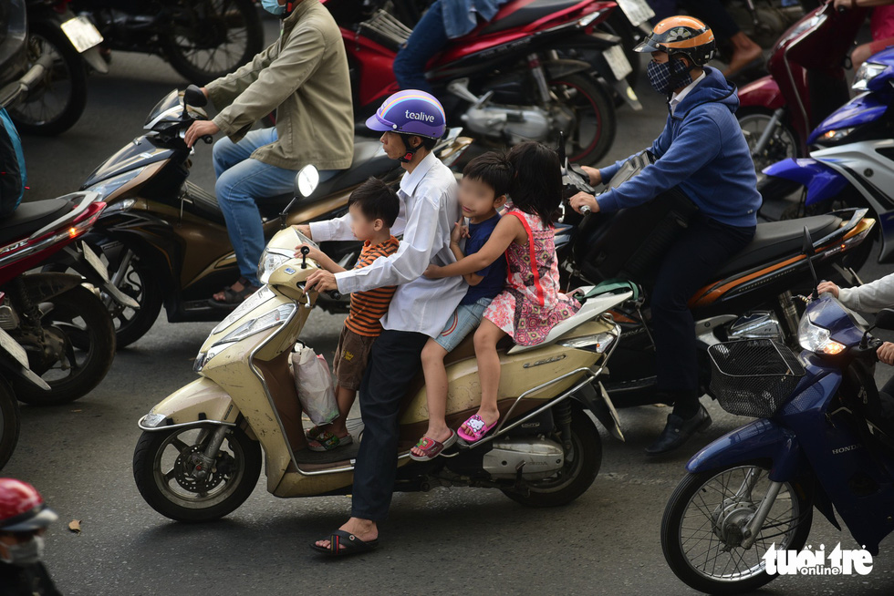 A man carries three children, who wear no helmet, on one vehicle in Ho Chi Minh City. Photo: Quang Dinh / Tuoi Tre