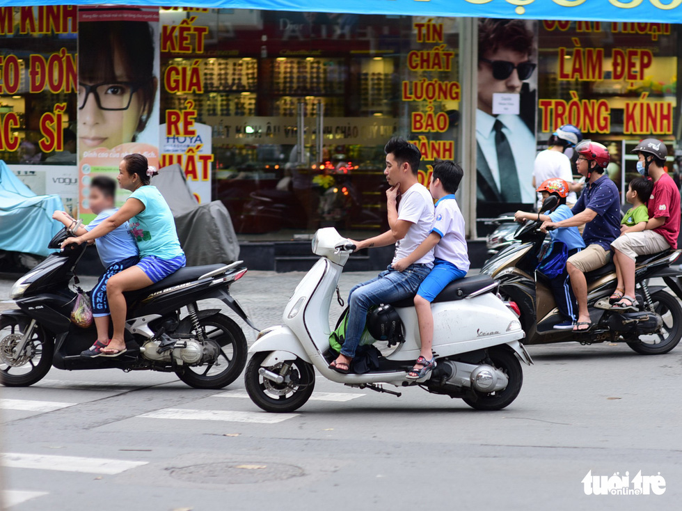 A man carries his child on a motorbike on Tran Quang Khai Street in Ho Chi Minh City, with helmets being hung on the vehicle instead of being worn by the two. Photo: Quang Dinh / Tuoi Tre