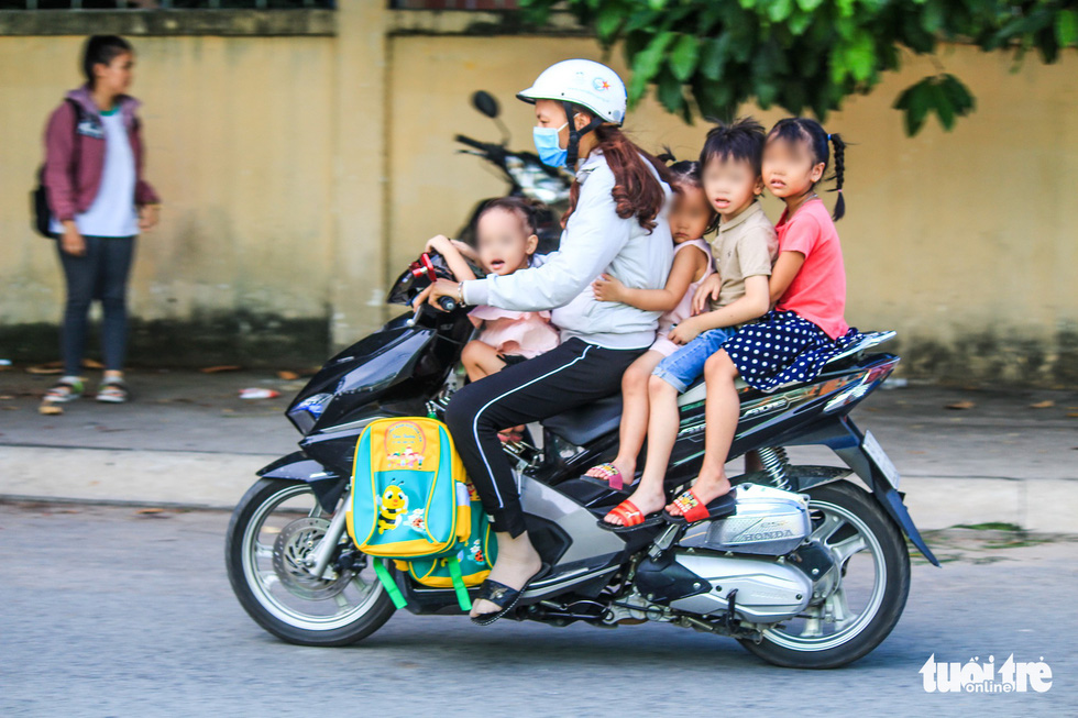 A woman carries four children, who wear no helmet, on one vehicle in Ho Chi Minh City. Photo: Quang Dinh / Tuoi Tre