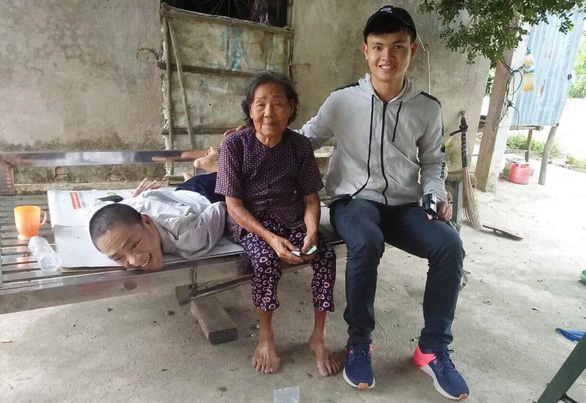 Pham Van Chau (right) smiles for a photo with Thuong, a man born with disability in Quang Ngai Province, central Vietnam. Photo: Supplied