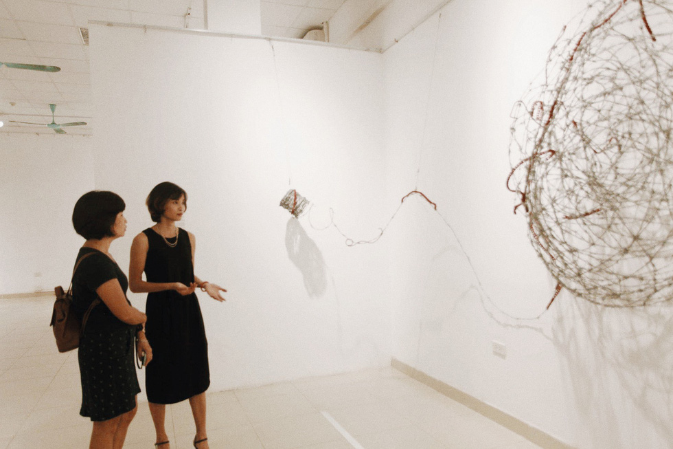 Artist Pham Thi Hong Sam presents the meaning of an art installation to a visitor at the Insect exhibition in Hanoi. Photo: Mai Thuong / Tuoi Tre