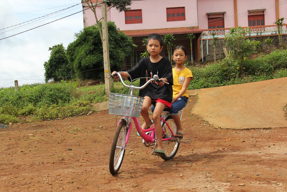 Nguyen Thi Diem Phuong (left) rides a bike with her younger sister in the back. Photo: Tran Mai / Tuoi Tre