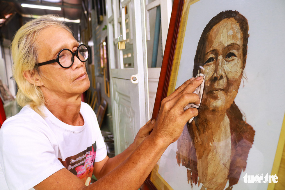 Le Van Nghia and a portrait of his late wife, made using lotus leaves Photo: Ngoc Phuong / Tuoi Tre