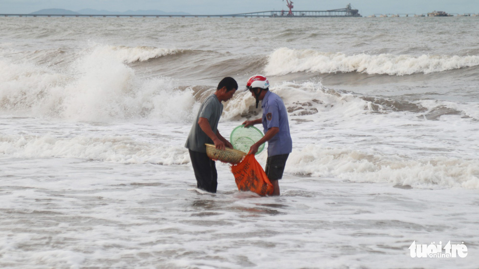 Two men catch shellfish after storm at Cua Lo Beach in north-central province of Nghe An, August 30, 2019. Photo: Doan Hoa / Tuoi Tre